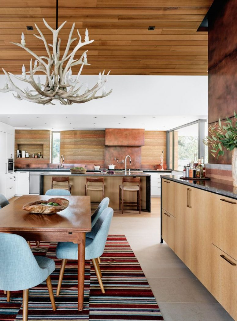 The kitchen and dining space are done in warm sandy shades and the design reminds of canyons