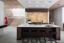 04 The kitchen is done with dark stained furniture, white stone countertops and a gorgeous quartzite backlit backsplash