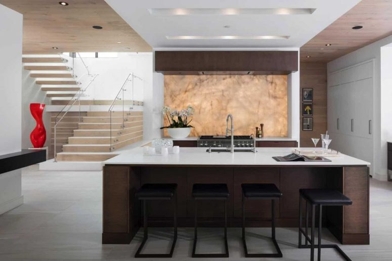 The kitchen is done with dark stained furniture, white stone countertops and a gorgeous quartzite backlit backsplash