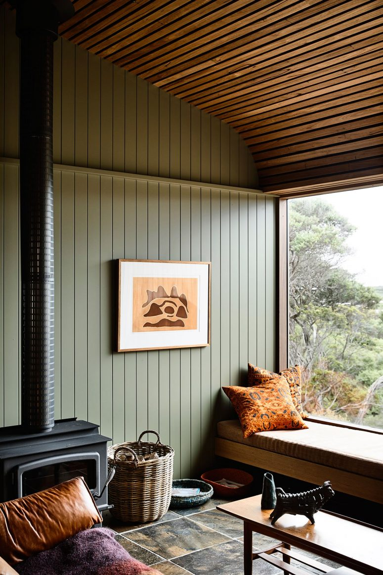 The living room features a wood slab ceiling, sage green wooden walls and a comfy window seat plus a hearth