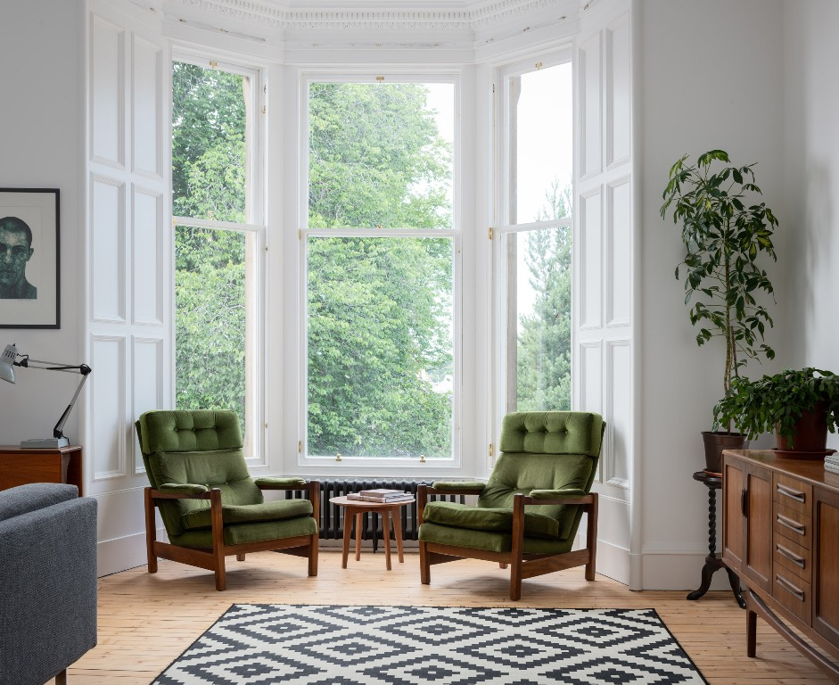 There's a bay window with a couple of green chairs, which is a great conversation space or a reading one
