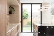 04 There's a large black terrazzo kitchen island highlighted with pendant lamps