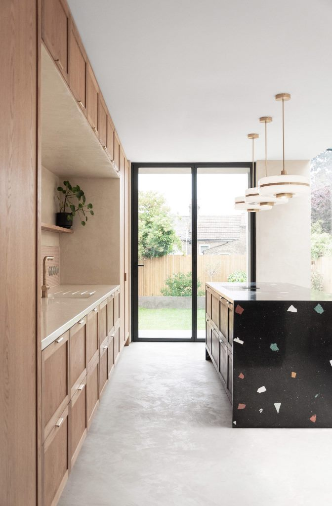 There's a large black terrazzo kitchen island highlighted with pendant lamps