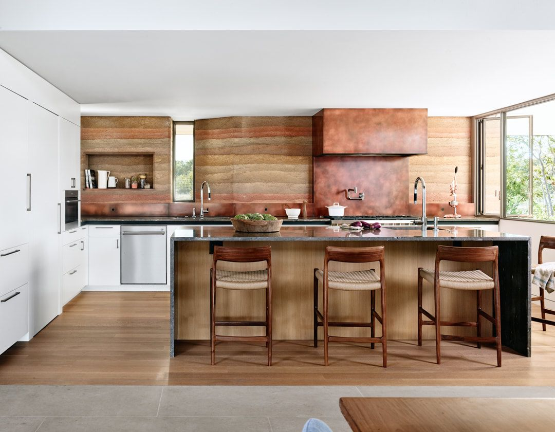 The backspalsh and hood are clad with copper to echo with the fireplace and highlight the color scheme
