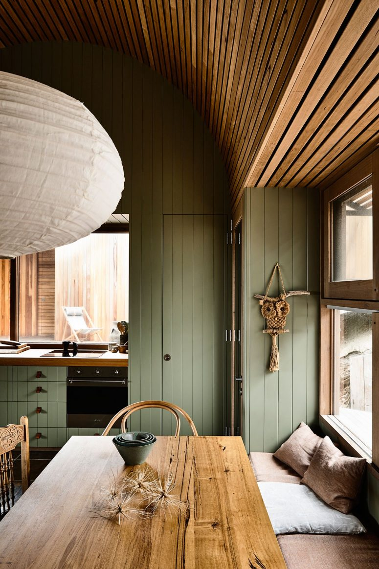 The kitchen and dining room are united into one space also clad with sage green wood and with matching furniture