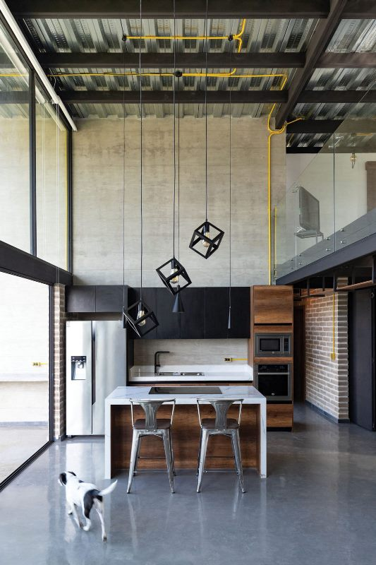 The kitchen is minimalist, it features black upper cabinets, a stained wood kitchen island and gorgeous pendant lamps