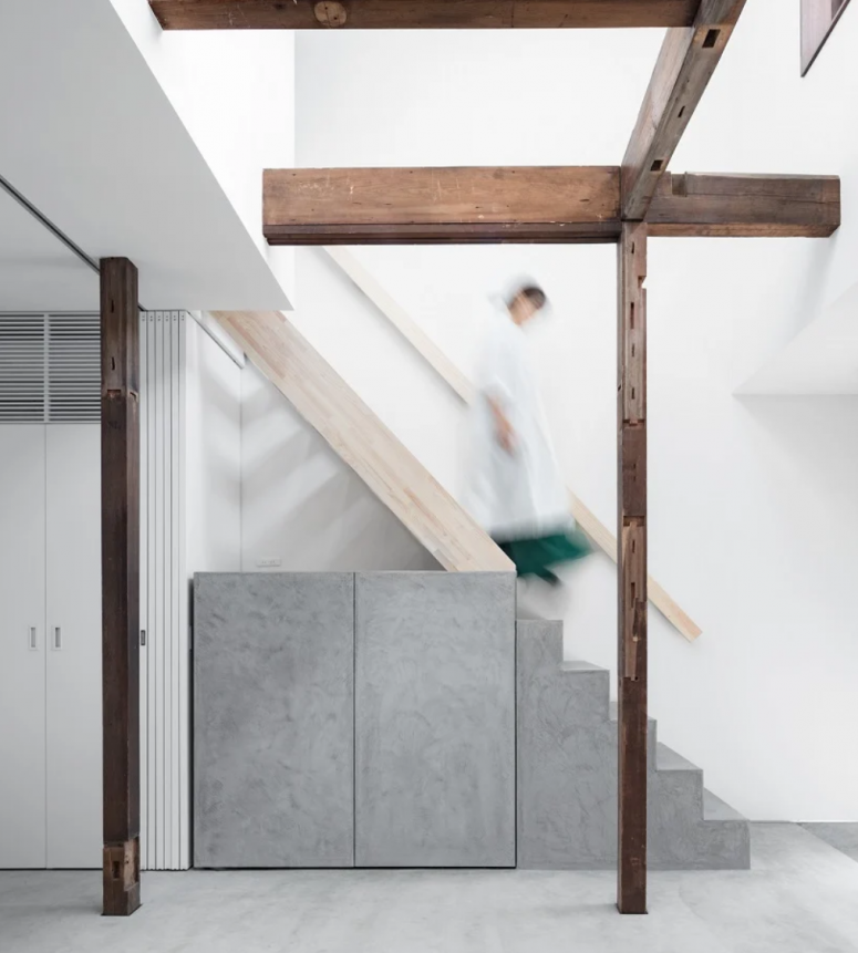 The staircase features a built-in grey storage unit under it to make use of this awakward space