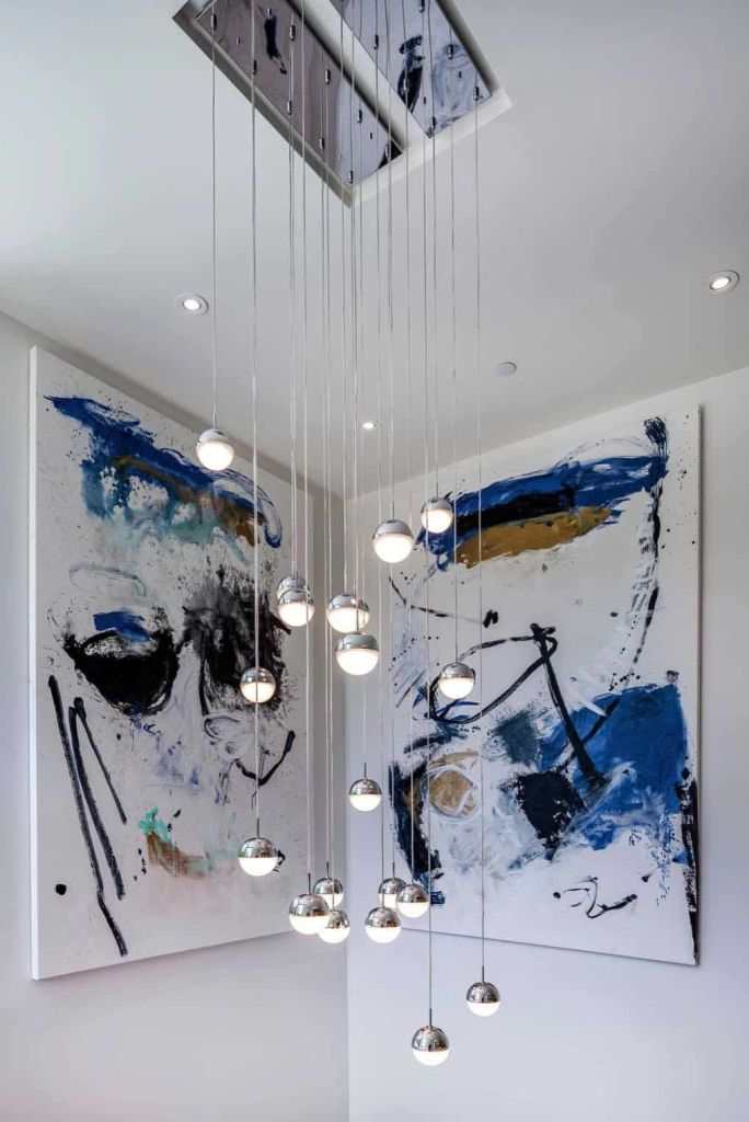 The staircase space is accented with bright artworks and pendant bubble lamps