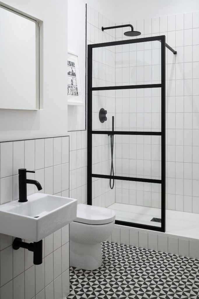 This bathroom is graphic and monochromatic, with matte black fixtures and cool mosaic tiles on the floor