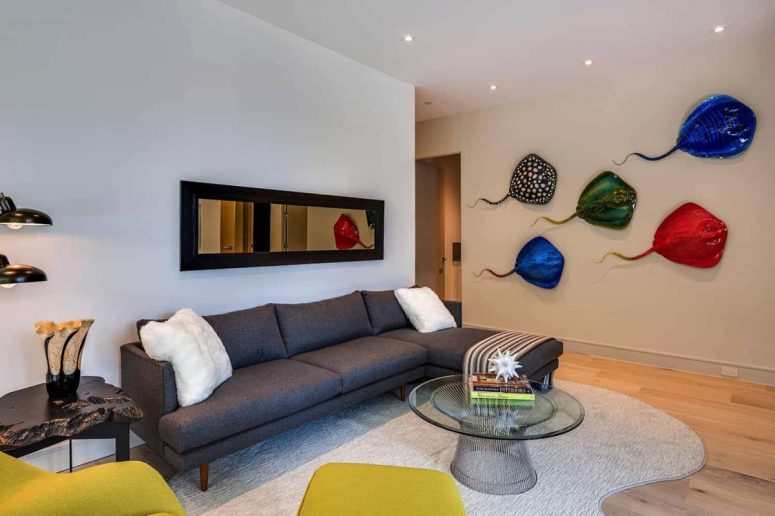 A second mini living room is done with elegant furniture, bright mustard pieces and colorful artworks on the wall