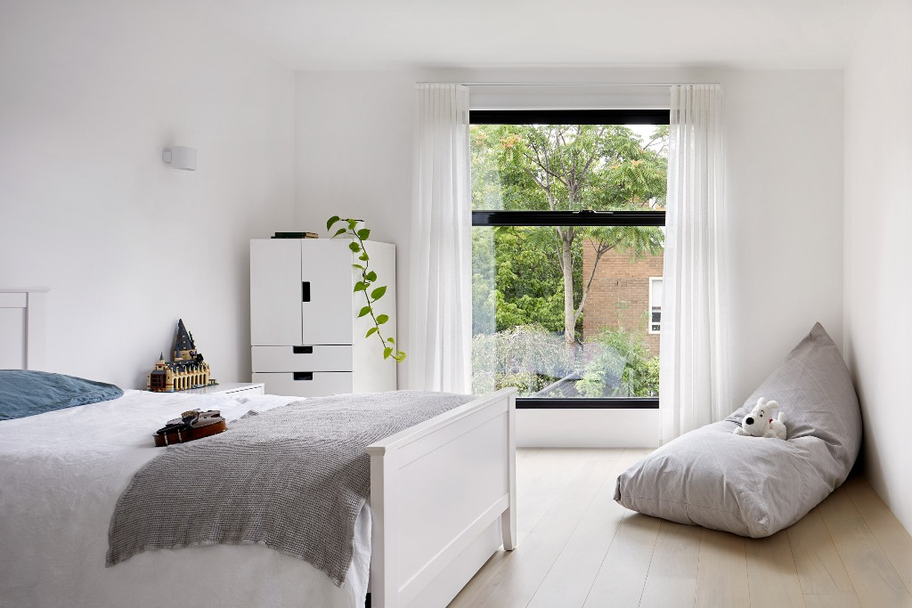 The kid's room is done in white, with several touches of muted colors and some greenery