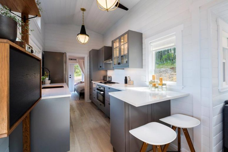The kitchen is done with grey cabinets, white countertops and there's a small breakfast bar