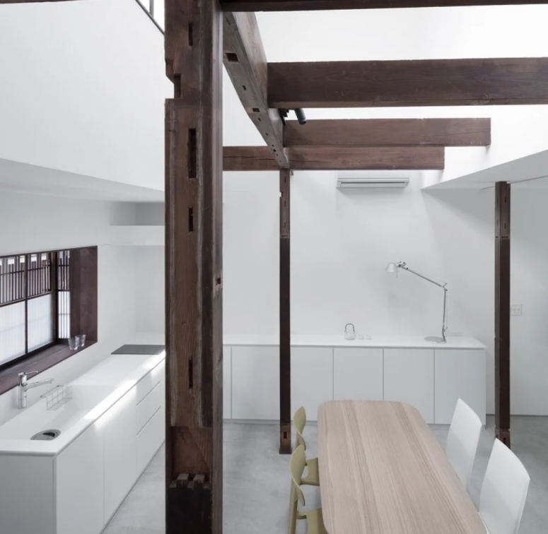 The kitchen is white and minimalist, and the dining space is also here, the original wooden structure adds interest to the space
