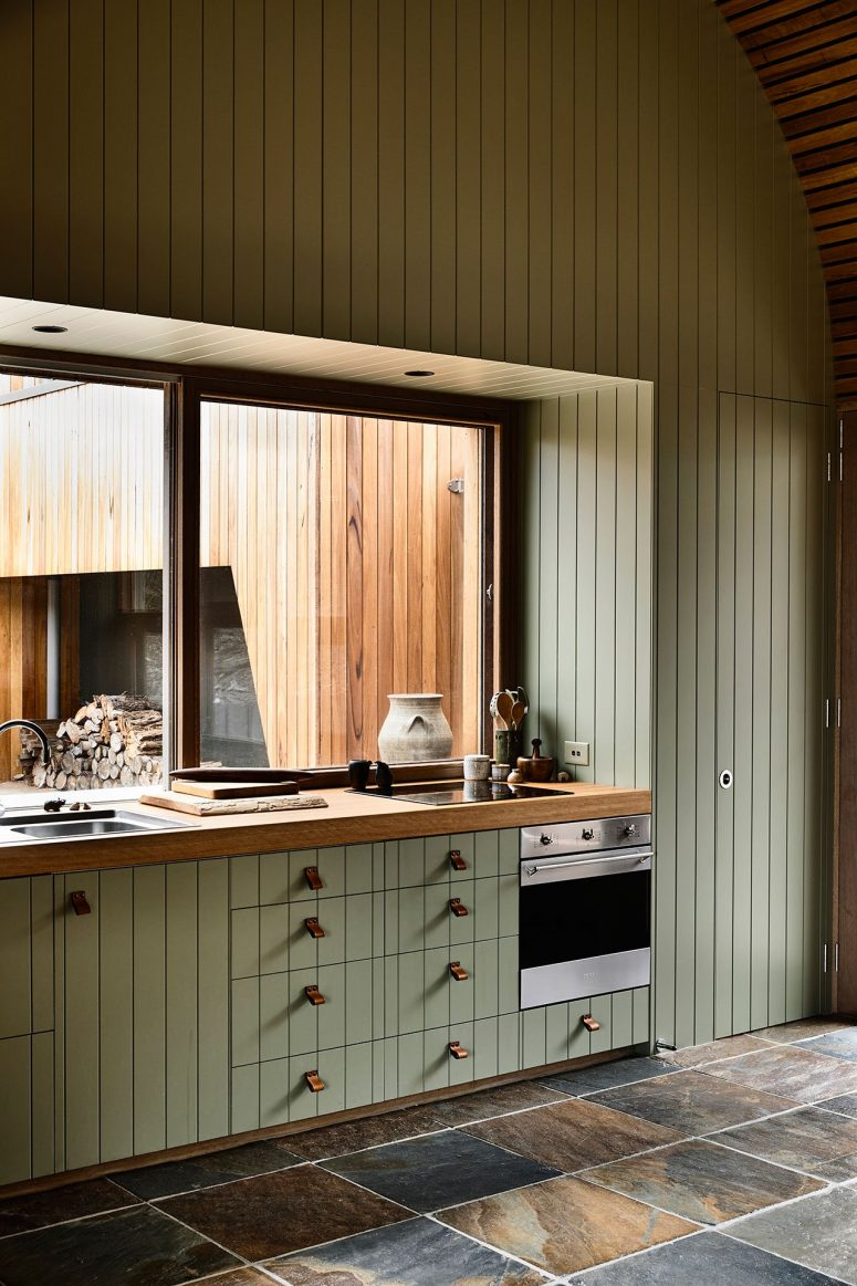 The kitchen shows off a large window instead of a backsplash and it brings much light inside