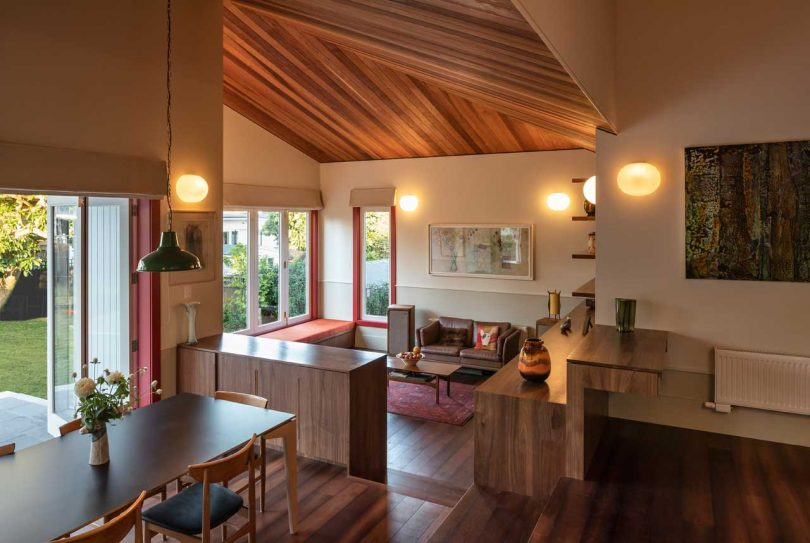 The living room is on a lower level, with a comfy ornage window seat, stylish mid century modern furniture and lights