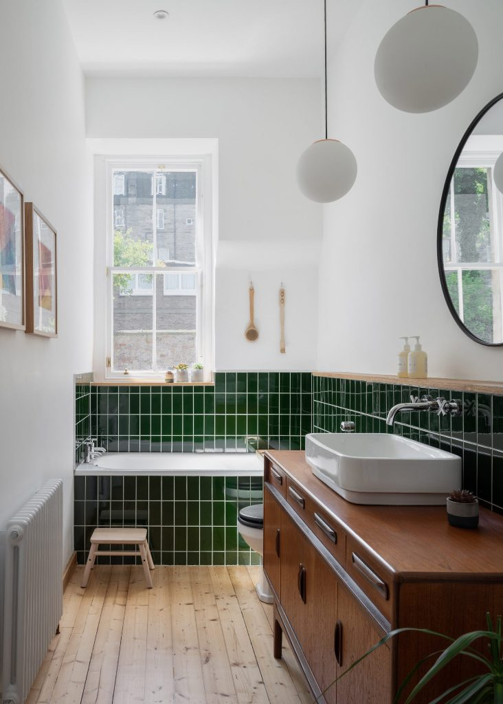 This bathroom shows off grass green tiles, light and rich stained wooden items