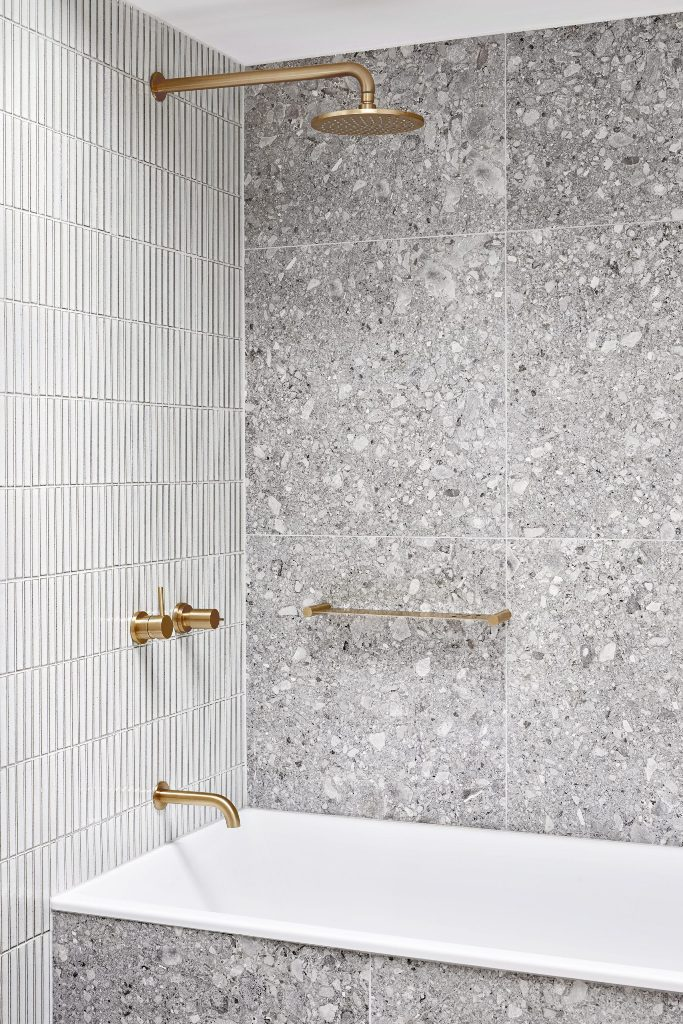 The bathroom is clad with grey stone and white skinny tiles and is accented with gold fixtures