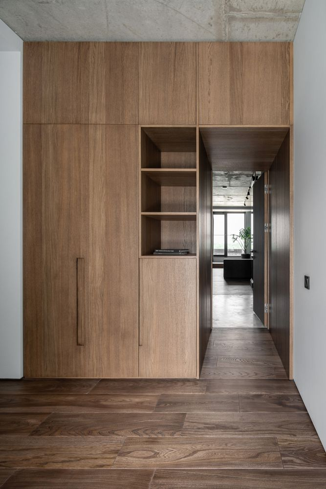 The bedroom is accessed through a small corridor lined with wood