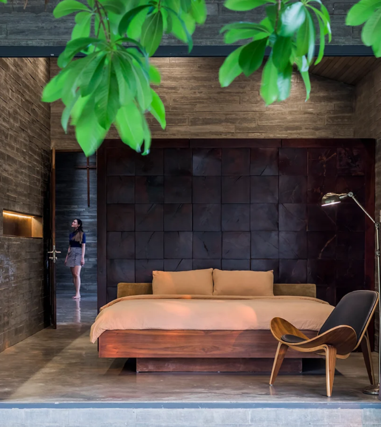The bedroom shows off woodgrain concrete boards, a gorgeous wood stained wall and chic wooden furniture