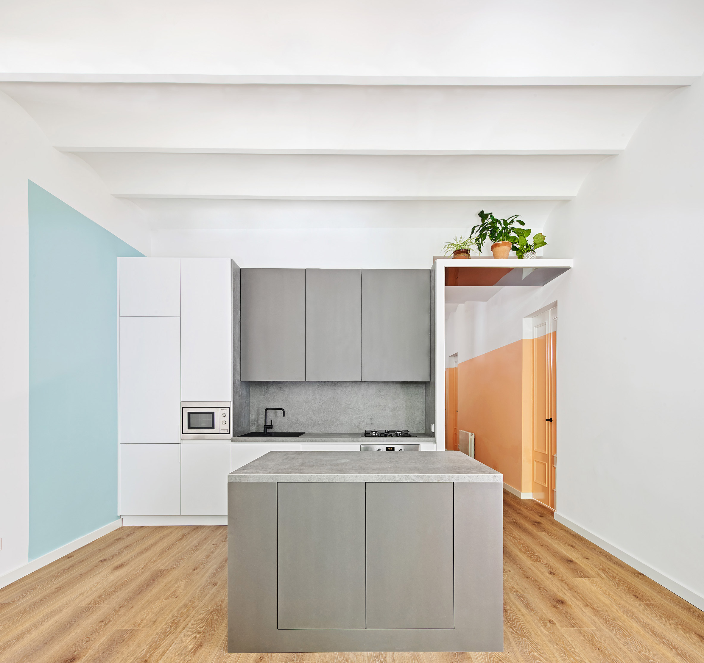 The kitchen also shows off color blocking with graphite grey furniture and a light blue square