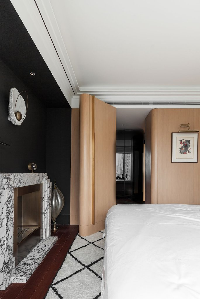 The master bedroom is done with neutral wooden panels, a marble fireplace and a black accent wall