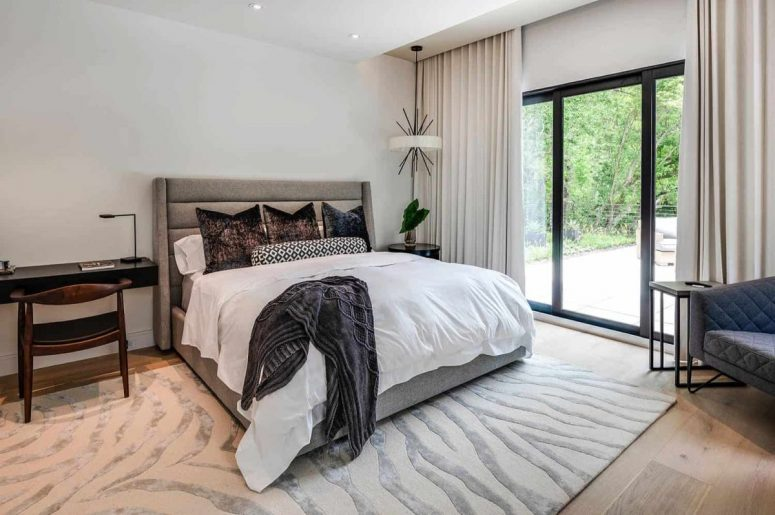The master bedroom is neutral, with chic furniture, built-in lights and much natural light, too