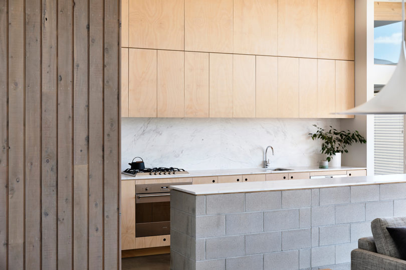 The plywood cabinets perfectly match those in the living room zone and make the space cohesive