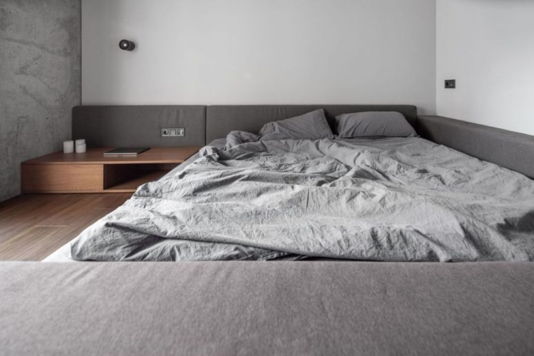The bedroom is very minimal, done in white and grey, with stained wooden items