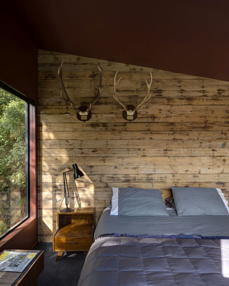 The bedroom is woodland-inspired, it features a wood paneled wall, antlers, some wooden furniture and a large bed