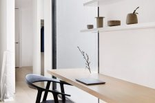 08 The home office shows off open shelves and a floating desk and there's a largre window to let more light in