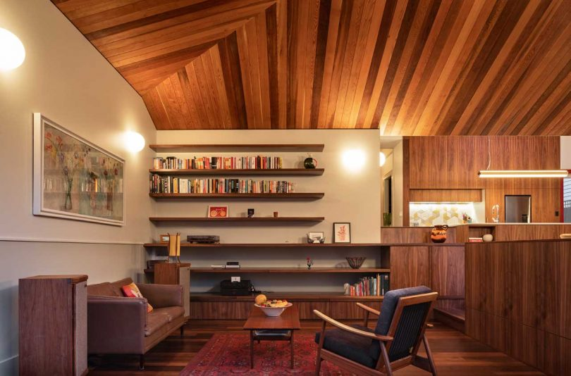 The living room shows off cool floating shelves that echo with the wooden clad ceiling