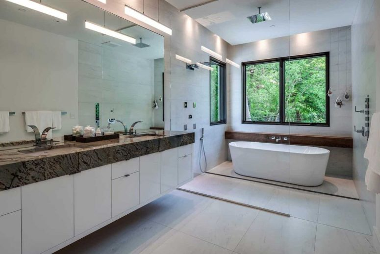 The master bathroom is also neutral, with a stone countertop that contrasts and lots of light
