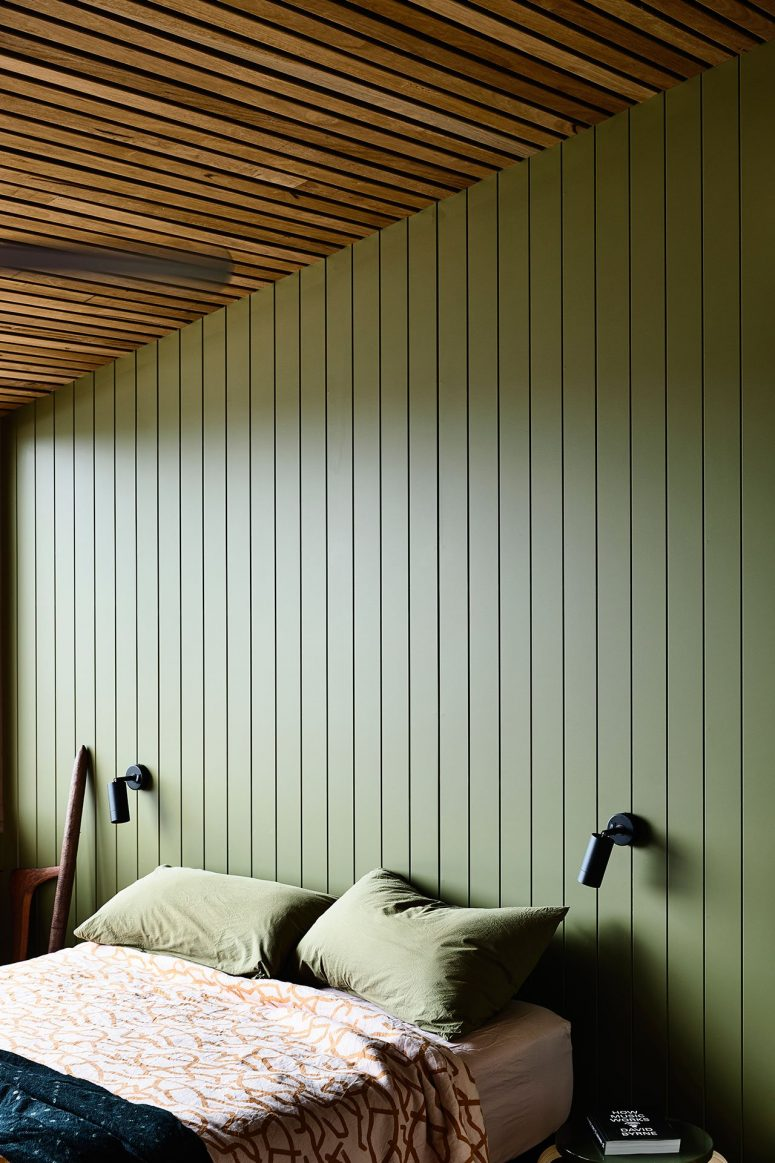 The master bedroom shows off sage green walls, a wood slab ceiling and comfy furniture