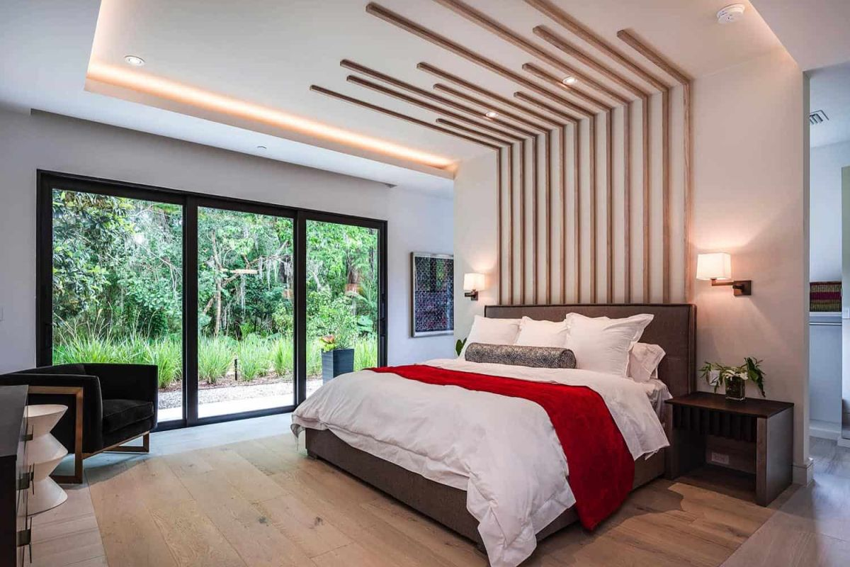Another bedroom shows off a cool extended headboard, lots of light and a glazed wall