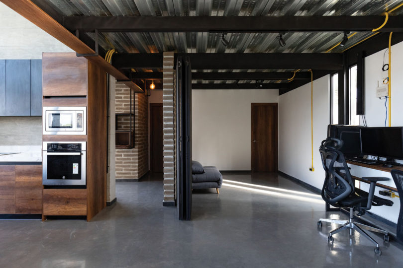 The furniture is dark and contemporary and you can see exposed brick walls here and there