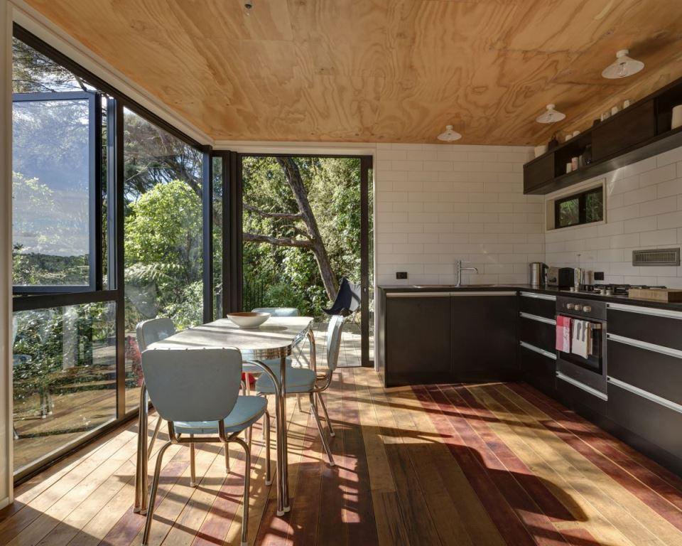 The kitchen is small and is done with black cabinets, there's a dining space by the glazed wall here