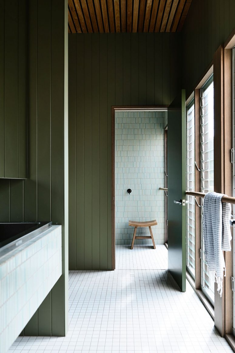 Another bathroom shows off neutral and green tiles that match sage green wood