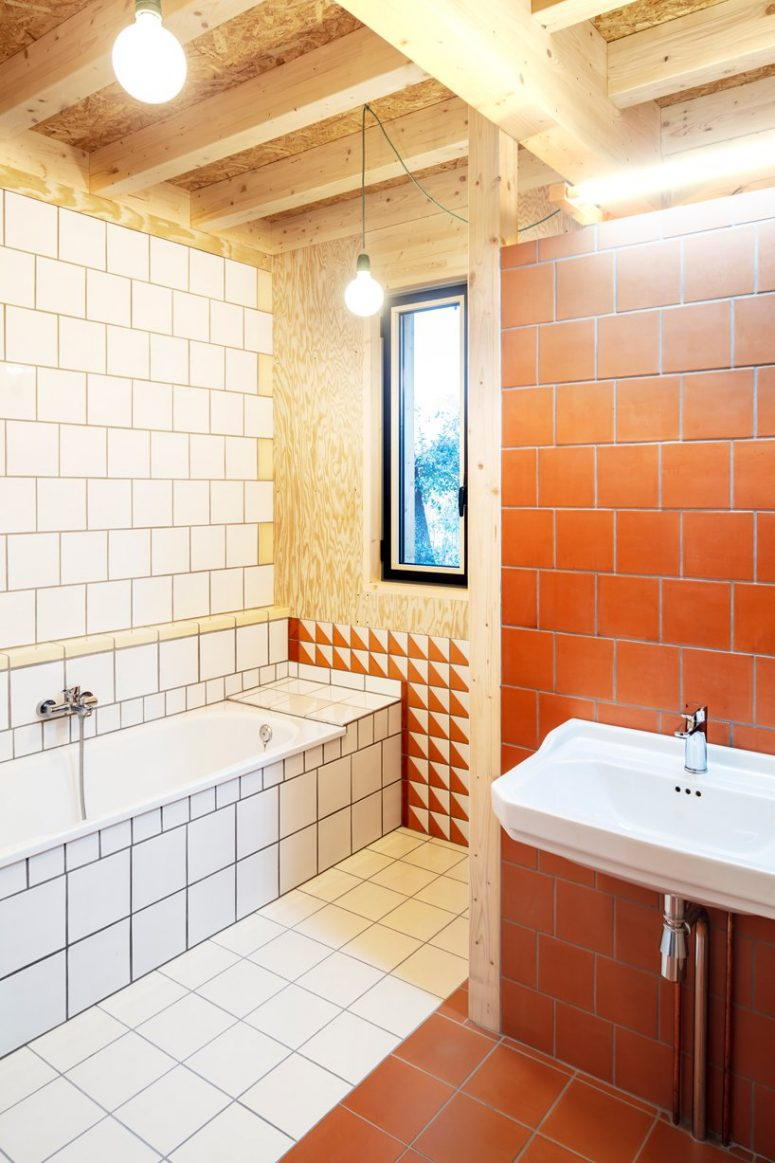 The bathroom is done with white and terracotta tiles and some timber again