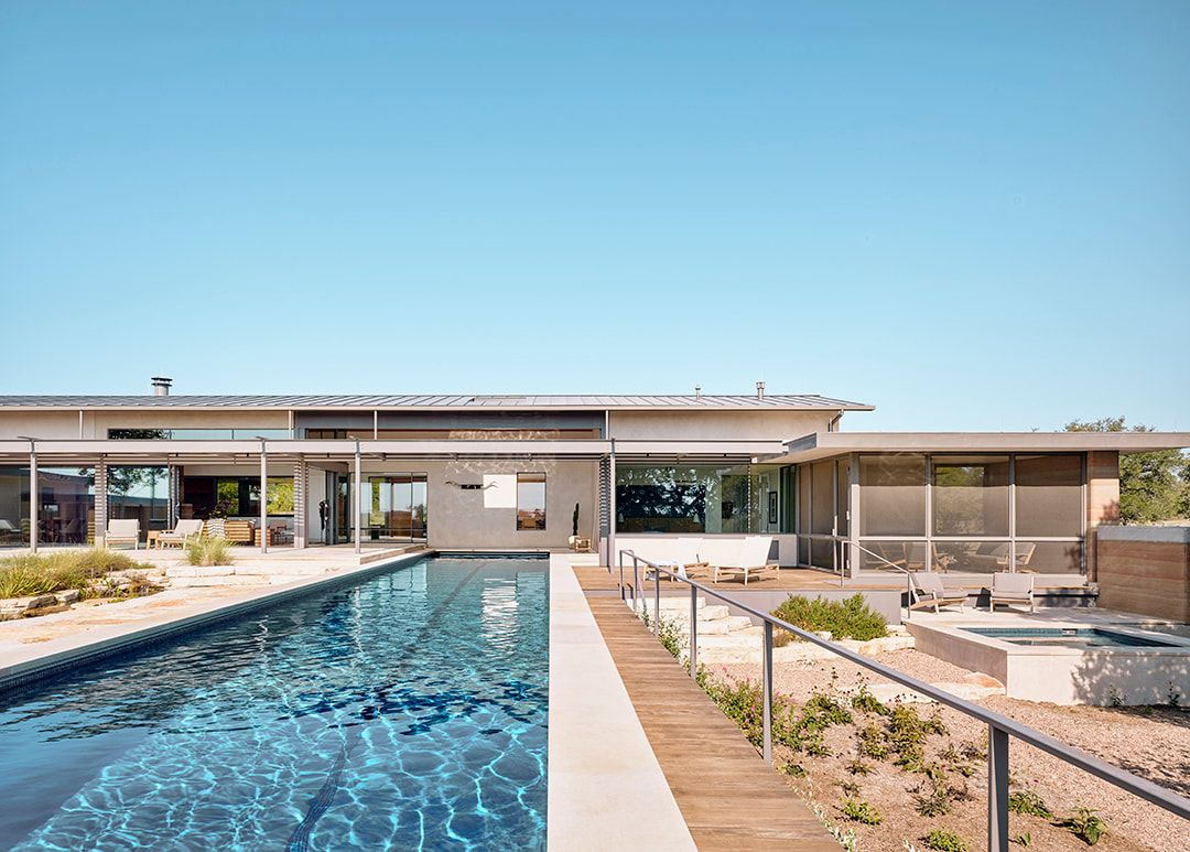 The pool is long and narrow and is clad in white for a laconic look