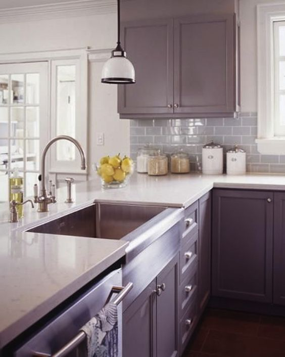 a contemporary lilac kitchen with a white countertop and a backsplash plus white pendant lamps