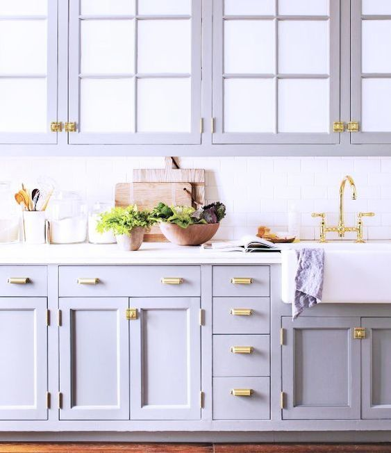 a cute lilac kitchen with a white tile backsplash and elegant gold handles looks very stylish and non-typical