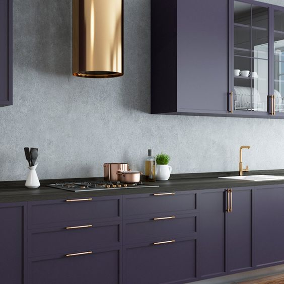 a dark purple kitchen with a grey stone backsplash, black stone countertops and touches of gold here and there