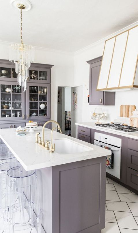a modern glam kitchen in lilac and white, with gold touches, a chic hood and a modern crystal chandelier over the island