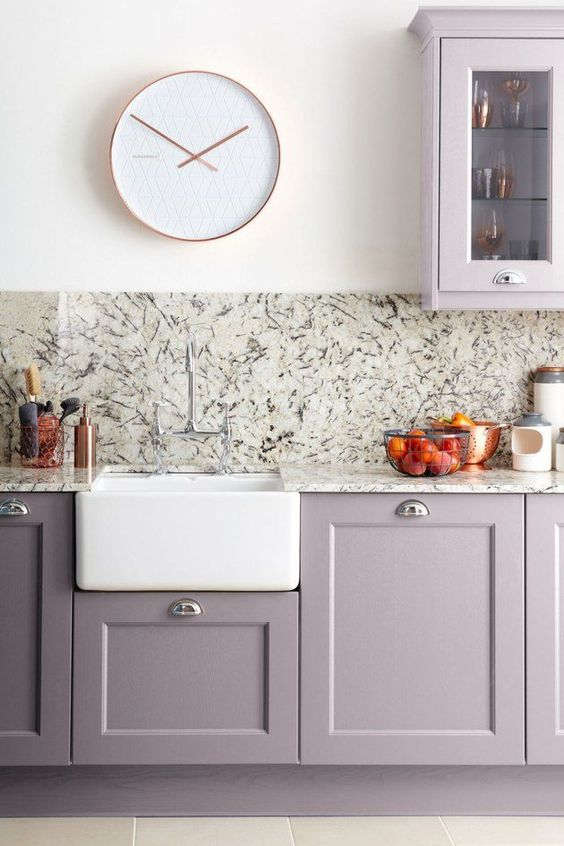 a modern grey lilac kitchen with stone countertops and a backsplash, with a white clock and sink looks very chic