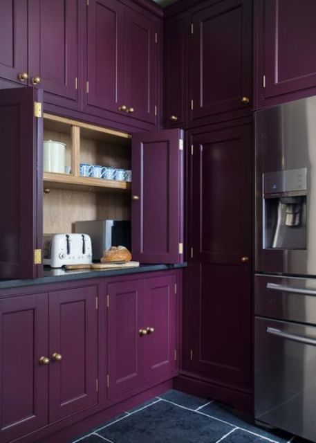 a moody vintage purple kitchen all clad with doors and panels and with gold knobs for an accent