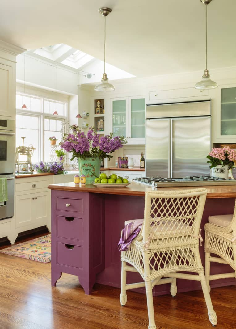 a neutral vintage farmhouse kitchen with a purple kitchen island, skylights and pendant lamps and some purple blooms