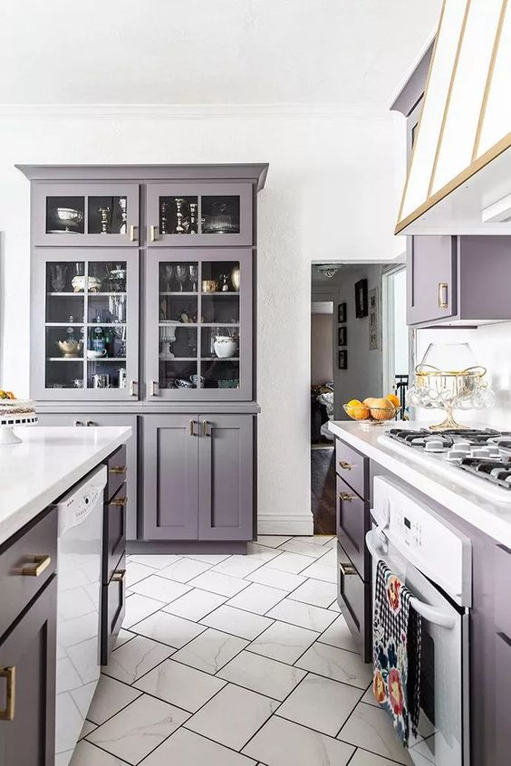 a purple kitchen with white touches to refresh it and some gold touches to make it super cool and chic
