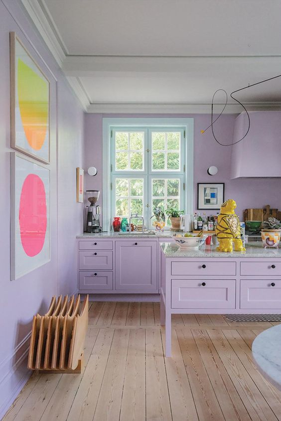 a quirky lilac kitchen with grey stone countertops and bright artworks on the wall is a very catchy space to be