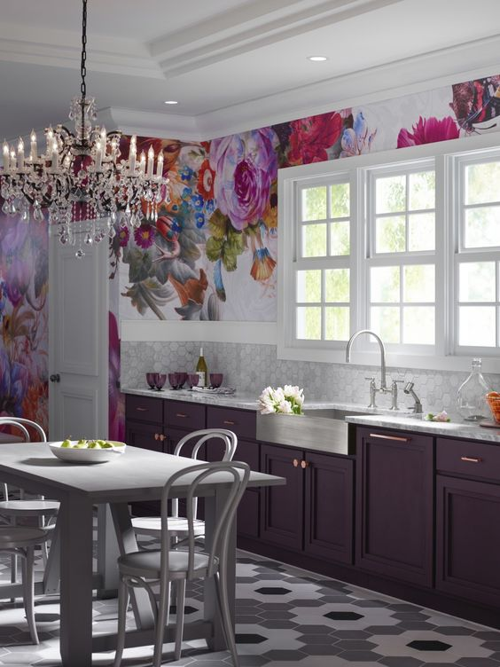 a refined purple kitchen with marble hex tiles, an oversized bright floral artwork and a crystal chandelier