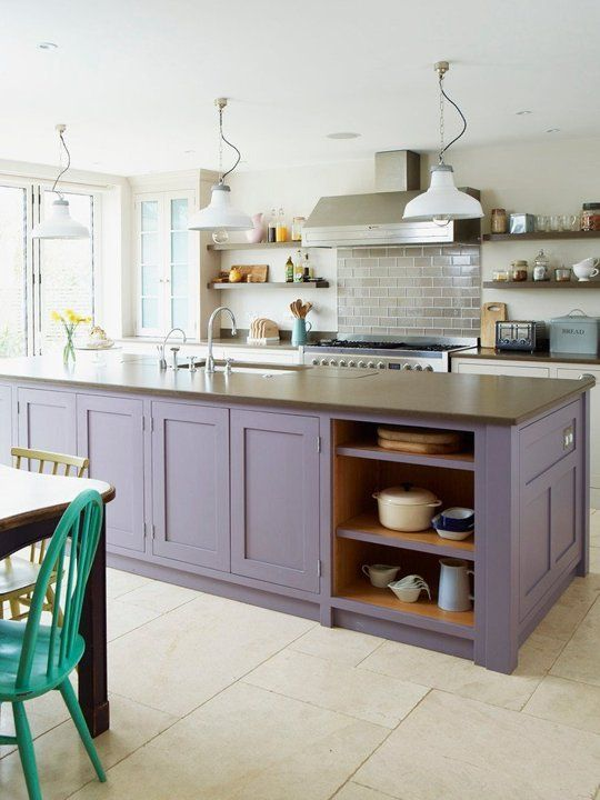 a stylish modern kitchen with white cabinets and a purple kitchen island plus stone countertops and white pendant lamps